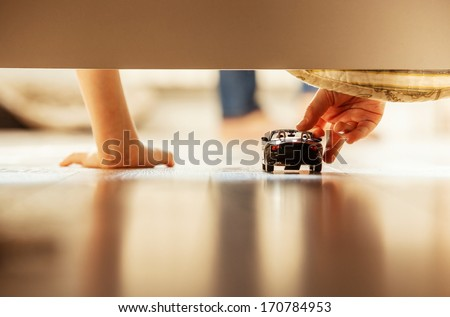 Boy playing with toy car overhang from the bed - stock photo