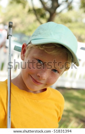 Boy plays golf in blue cap - stock photo