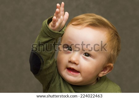 Boy pointing forward with a determined and inspired expression on a neutral background - stock photo