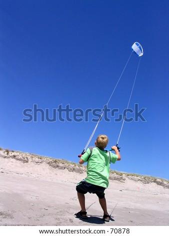Boy practicing kite surfing - stock photo