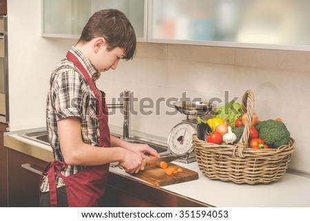 boy prepares vegetables in the kitchen - vegetarian healthy people - stock photo