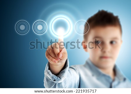 Boy pressing a virtual touch screen. Blue background. - stock photo