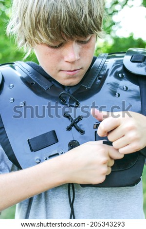 Boy putting his football gear on - stock photo