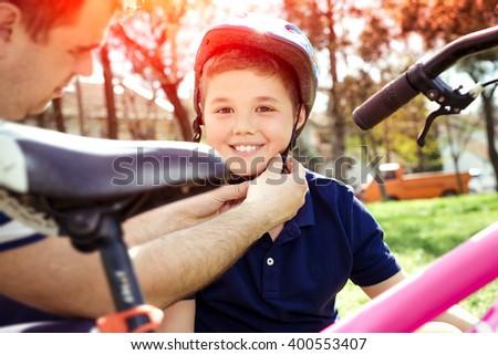 Boy putting on a bike helmet - stock photo