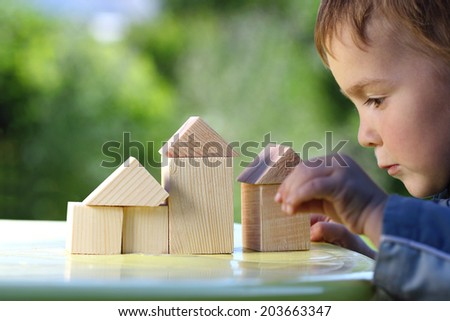 boy raises his hand to the house from wooden cubes - stock photo