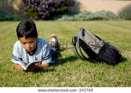 Boy reading a book lying on the grass. - stock photo