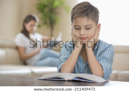Boy reading book with mother in background at home - stock photo