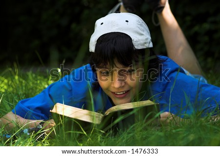 Boy reading in the park on a sunny day - stock photo
