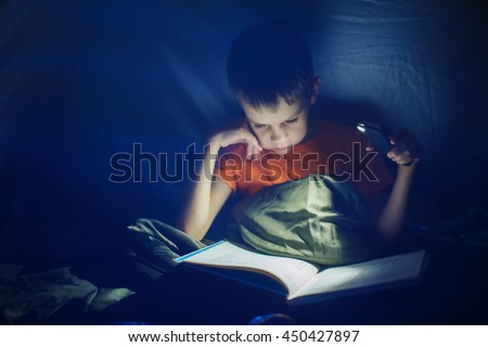 boy reading in the tent at night. child reads a book in the tent by the light of a mobile phone. selective focus - stock photo