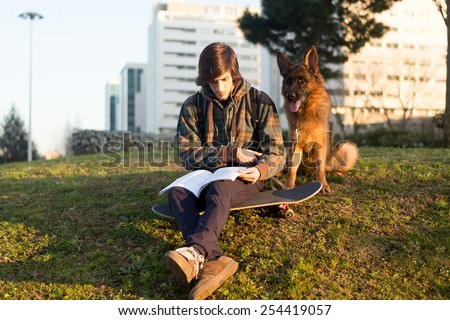 Boy relaxing at the city park at the sunset - stock photo