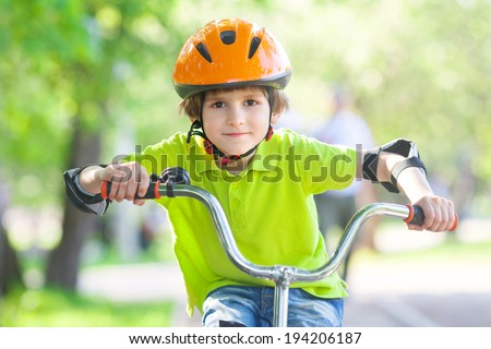 boy rides a Bicycle in summer Park - stock photo