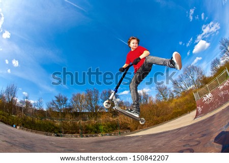 Boy riding a scooter is jumping at a scooter park - stock photo