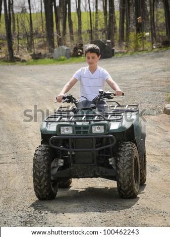 Boy riding ATV - stock photo