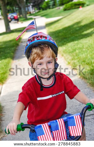 Boy riding his bicycle in a 4th of July neighborhood parade. - stock photo