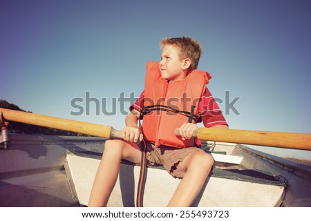 Boy rowing a boat on a lake - stock photo