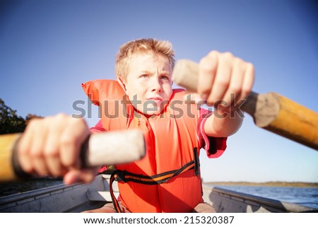 Boy rowing a boat on a lake. Instagram effect - stock photo