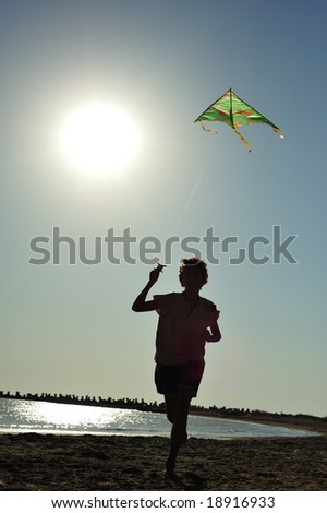 Boy running and flying a kite - stock photo
