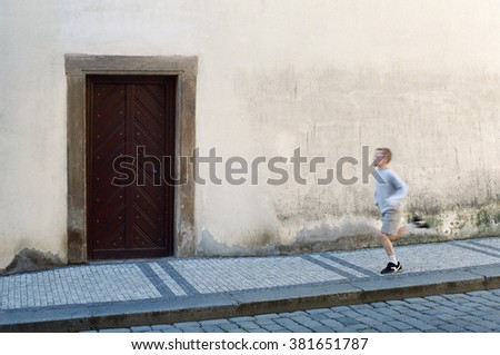Boy running at the pavement with heavy wooden door in front.  - stock photo