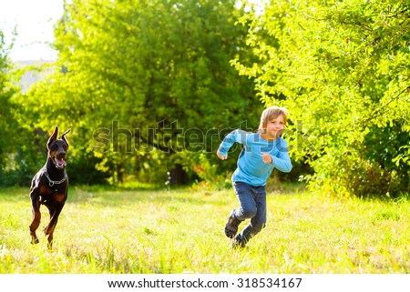boy running away from dog or doberman in summer park - stock photo