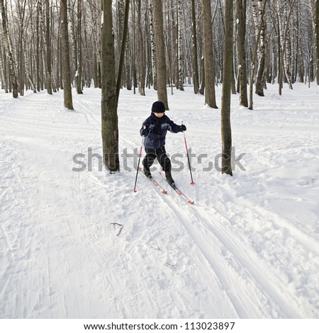Boy running on skis in winter forest - stock photo