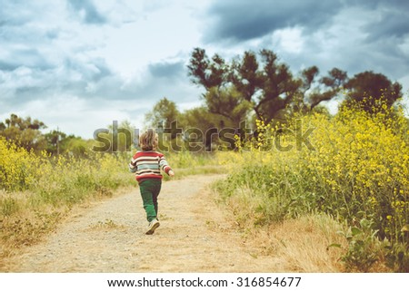 Boy running on the meadow road. Instagram filter applied. - stock photo