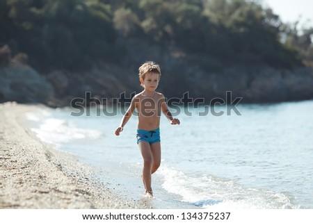 Boy running sea - stock photo