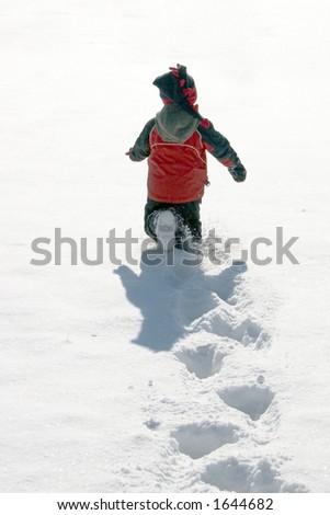 Boy running through snow - stock photo