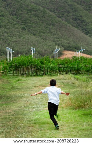 Boy running to group of wind turbines - stock photo