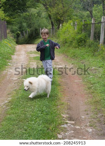 boy running with a dog - stock photo