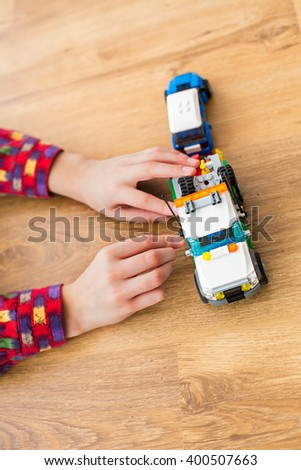 Boy's hands move toy truck. Child playing with toy vehicle. Technicians need to hurry. Power of imagination. - stock photo