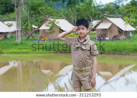 boy scout, a Thai Asian boy scout in uniform with cheerful smile stand at salute - stock photo