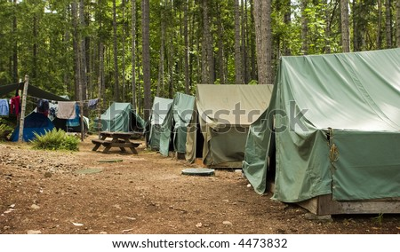 Boy scout campground. A typical campsite at a Boy Scout Camp includes tents, a table, dirt, and dirty clothes drying on a rope. - stock photo