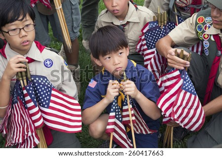 Boy scout placing 85, 000 US Flags at Annual Memorial Day Event, Los Angeles National Cemetery, California, USA, 05.24.2014 - stock photo