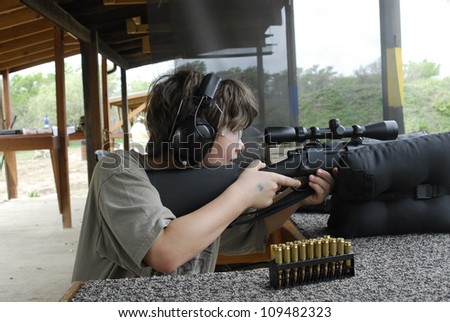 Boy shooting a gun - stock photo