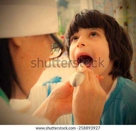 boy showing his throat to doctor pediatrician. instagram image retro style - stock photo