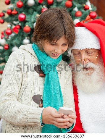 Boy showing smartphone to Santa Claus in front of Christmas tree - stock photo