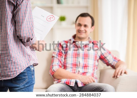 Boy showing to his father perfect test result. - stock photo