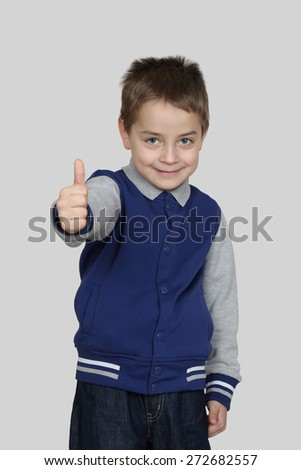 Boy shows thumb up on gray background - Endorsement, all is good - stock photo