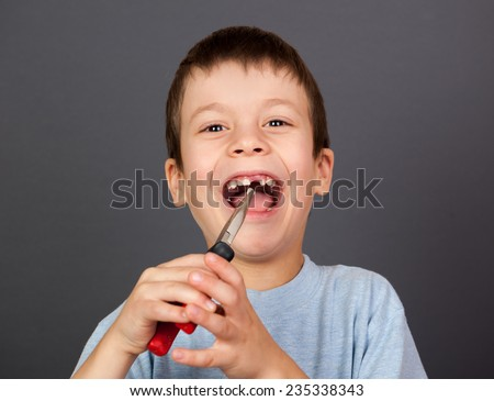 Boy simulates tooth removal with pliers - stock photo