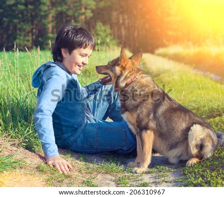 Boy siting and talking to dog in the meadow - stock photo