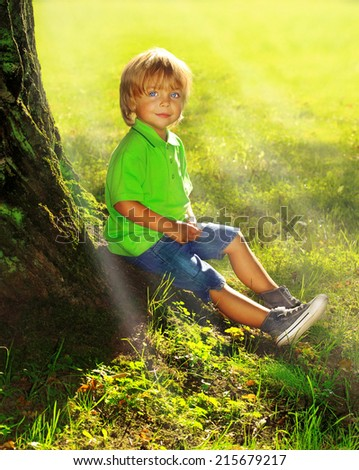 Boy sits near tree in the forest. - stock photo