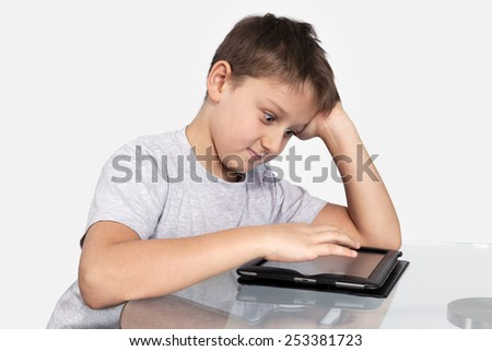 Boy sitting at a glass table resting his head on his hand, fingers touch tablet computer. What he saw surprised him. Isolated on gray background - stock photo