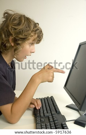 Boy sitting at computer pointing at the screen - stock photo