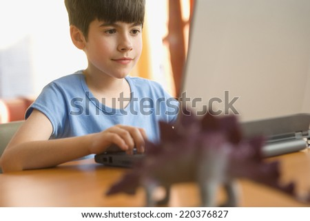 Boy sitting at desk with computer - stock photo