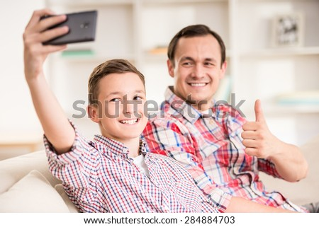 Boy sitting at sofa with father and making selfie. - stock photo