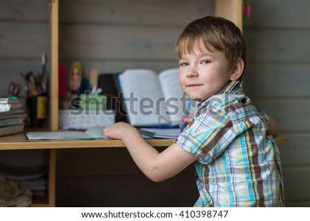 Boy sitting at table doing homework. Looking at the camera. - stock photo