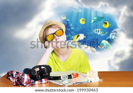 Boy sitting by the table and dreaming of snorkeling vacations - stock photo