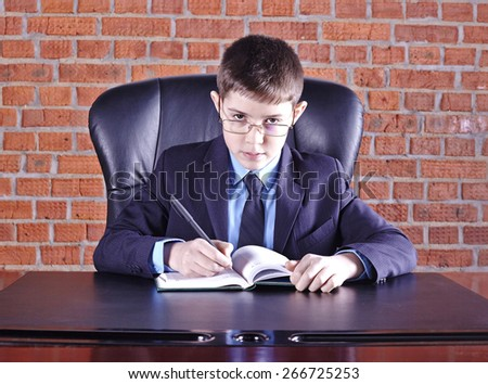 Boy sitting in a chair at the boss's table - stock photo