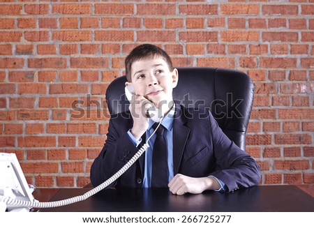 Boy sitting in a chair at the boss's table talking on the phone - stock photo