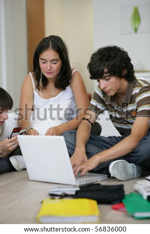 Boy sitting in front of a laptop computer near two girls listening to music - stock photo